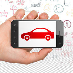 Vacation concept: Hand Holding Smartphone with Car on display