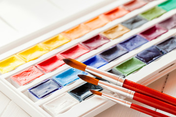 Brushes for water color painting and set of watercolor paints on
