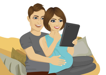 young pregnant couple sitting on sofa using tablet computer