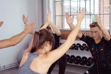 trainer und kunden beim ems-workout im fitness-studio