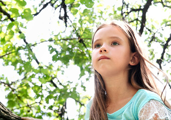Cute little girl in looking away in summer day outdoor