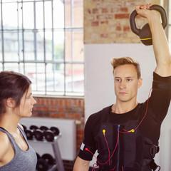 sportler stemmt kettleball beim ems-training