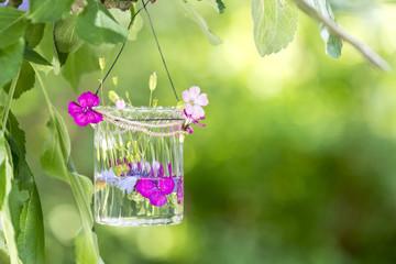 Blumen im Glas an einem Baum im Garten