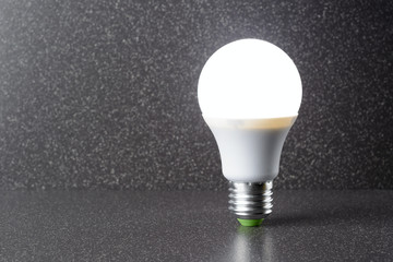 LED bulb standing on a ceramic tile