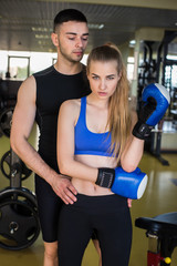 Muscular man and beauty girl posing in gym