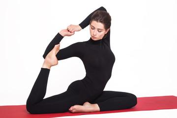 Beautiful athletic girl in black suit doing yoga. eka pada rajakapotasana asana - pigeon pose royal. Isolated on white background.