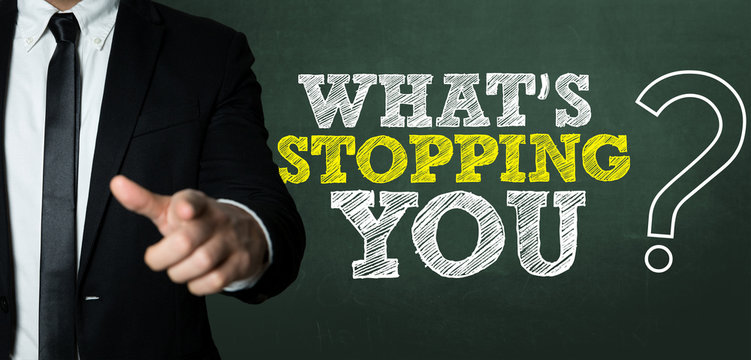 Business man pointing with the text: Whats Stopping You?