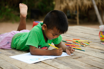 cute little boy is drawing with colour pencil at old home