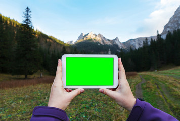 Hands holding white tablet with a green screen, mountain background