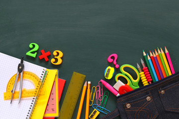 Back to school concept. School supplies on blackboard.