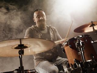 Silhouette of the drummer on stage. Dark background, smoke, spotlights