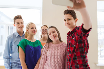 group of students taking selfie with smartphone