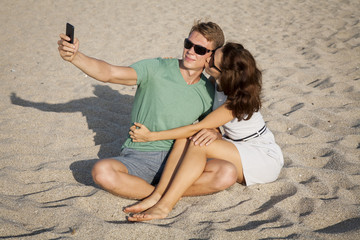 Young loving couple sitting on the sand at the beach and make selfies.