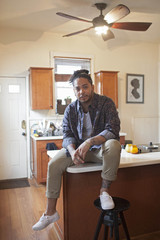 Young man sitting on a kitchen countertop