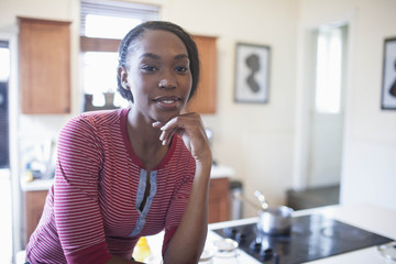 Portrait of young woman sitting on countertop in kitchen
