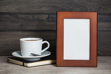 blank frame poster on the wooden table with cup of coffee and book