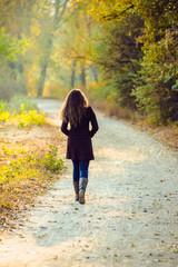 girl walks in beautiful autumn park