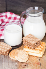 Milk and cookies on wooden background, dessert