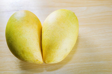 two mangoes in heart shape on wood background
