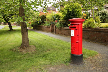 Victorian red post box on a residential tree lined street in Wilmslow, United Kingdom