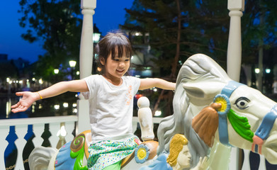 Happy Japanese girl on a horse carousel with no hand