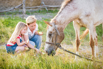 Mother and daughter feeding a horse an apple in the stud.
