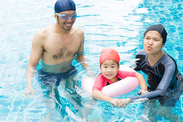 Little baby in an early swimming class with family