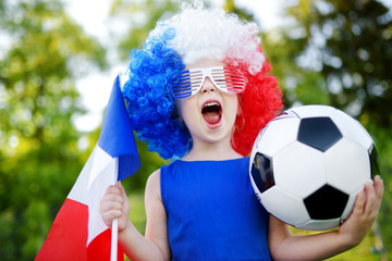 Funny little girl supporting and cheering her national football team