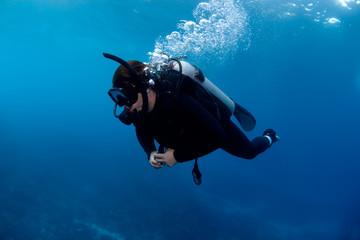 Scuba diver exploring deep reef.