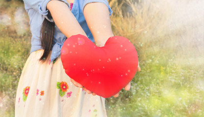women hold big red heart in wonderful glitter bokeh shining