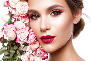 Portrait of young beautiful woman with stylish make-up and colorful roses around her face