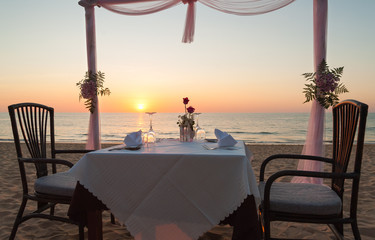 romantic dinner setup ,on the beach with sunset