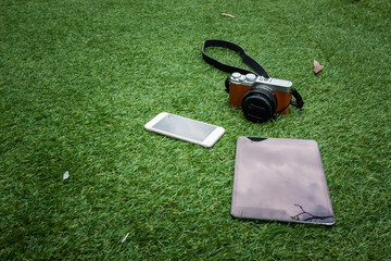 Camera, tablet and smartphone on a grass background