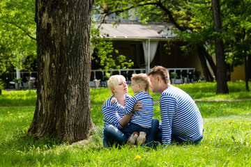 Happy family: mother, fathe and son in identical striped shirts in the park on a sunny summer day