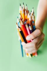 Child holding many colorful pencils