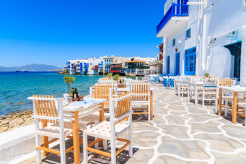 Chairs with tables in typical Greek tavern in Little Venice part of Mykonos town, Mykonos island, Greece Fototapete