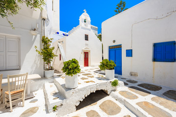 Square with church on whitewashed street with typical Greek architecture in beautiful Mykonos town,...