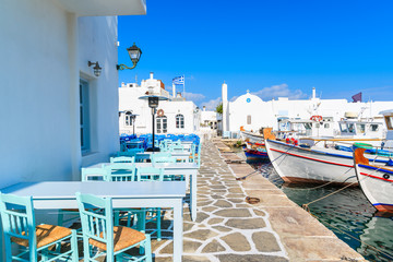 Taverna tables and typical Greek fishing boats in Naoussa port, Paros island, Cyclades, Greece