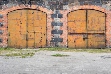 Pair of old rustic metal doors with red brick wall background