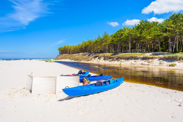 Fototapete - Kayaks on white sand beach in Debki village where Plasnica river has its estuary to Baltic Sea, Poland