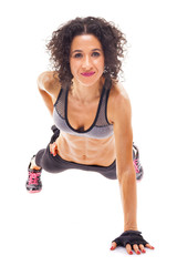 Fit woman making push ups with one arm, isolated on white backgr