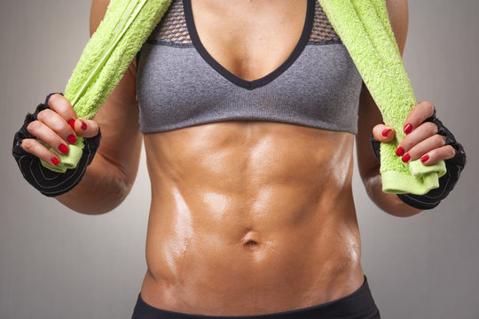 Fit woman posing with a green towel on grey background