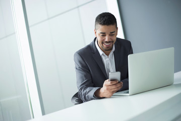 Handsome happy young businessman using mobile phone