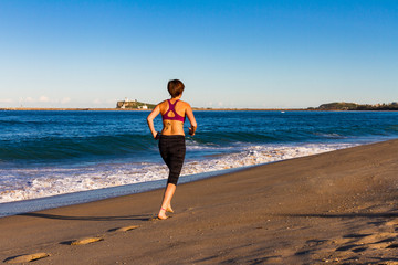 Young woman is jogging on a Beach