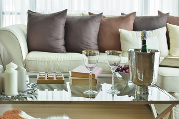 Wine glasses and wine bottle on table with beige sofa with dark brown pillows in modern classic living room