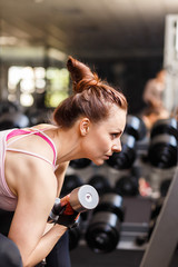 Athletic girl doing exercise with dumbbells in gym