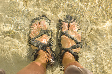Feet wearing sandals on shallow ocean photo