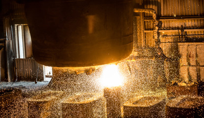 Steelworker pours liquid metal into molds from tank