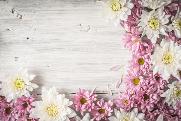 Frame of  white and pink flower on the white wooden table horizontal