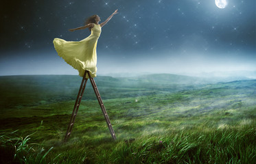 Frau greift nach den Sternen